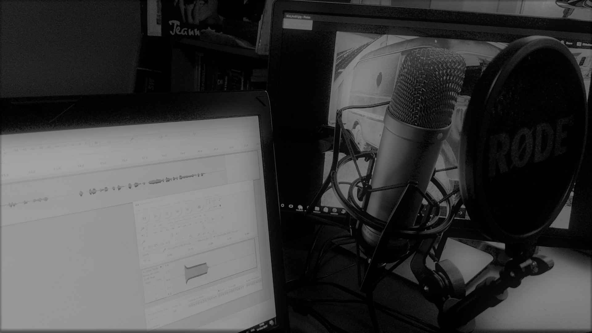 A microphone beside a computer screen showing a sound-editing software.